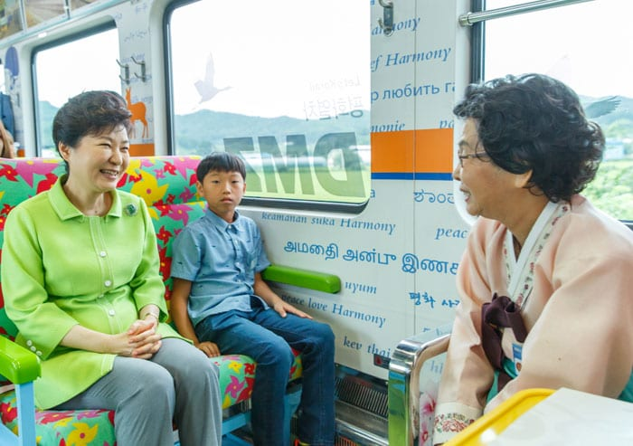 President Park Geun-hye (left) chats with passengers onboard the Gyeongwon Line on Aug. 5.