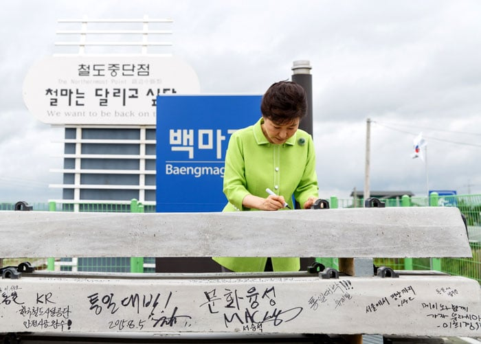 President Park Geun-hye signs one of the railway ties at Baengmagoji Station in Cheorwon-gun County, Gangwon-do Province, on Aug. 5.