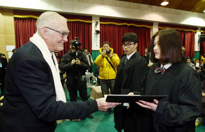 Chairman Brent Jett of the 40th Division Korean War Veterans association presents a graduation certificate to a student during the graduation ceremony.