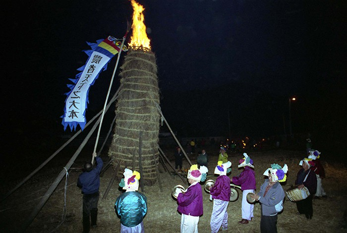 People perform some <i>nongak</i> farmers' music in 1993 in front of a large <i>daljip</i> bonfire (달집) on the night of Jeongwol Daeboreum, the first full moon of the lunar year. A large flag hanging on the bonfire says that, 'Farmers are the great foundation of the world.' In a traditional, agrarian Korea, people lit the straw structure on fire to remove any misfortune and to wish for a good harvest.
