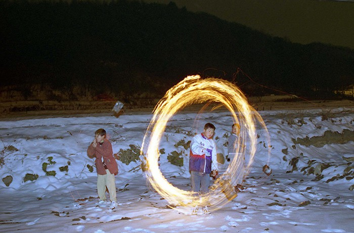 Kids enjoy a <i>jwibulnori</i> (쥐불놀이), a bundle of dried grass tied to a string and set on fire, on the night of Jeongwol Daeboreum in 1998. This folk game was used to help burn the fields and to remove mice and harmful insects from the farms before seeding, all in the hopes of having a good harvest.
