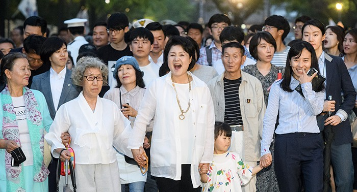 First lady Kim Jung-sook (center) and a crowd on June 26 walk along the pedestrian road in front of Cheong Wa Dae.