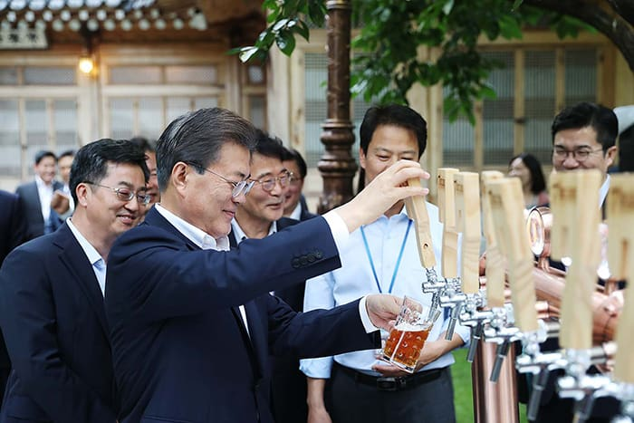 President Moon Jae-in (second from left) fills a glass of beer during a meeting with business leaders at Sangchunjae Hall in Cheong Wa Dae on July 27. All the beer served was hand-brewed by small- and medium-sized firms.