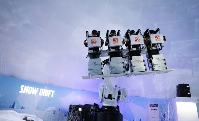 People in a robotic 'snow drift ride' enjoy running down a snowy mountain in VR, at the 'Igloo Festival with ICT' on Jan. 30.