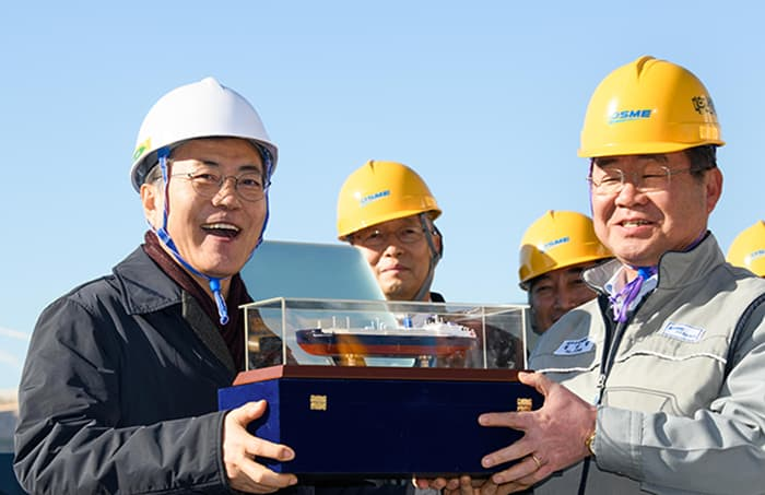 President Moon Jae-in (left) smiles as he receives a model of the icebreaker LNG carrier tanker 'Vladimir Rusanov' from Daewoo Shipbuilding and Marine Engineering CEO Jung Sung-leep, at Daewoo's Okpo Shipyard in Geoje, Gyeongsangnam-do Province, on Jan. 3.