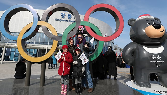 Berky Bruso (second from left) and her family pose for a photo at the Olympic symbol and Bandabi, the mascot for 2018 Paralympic Winter Games, in front of Gangneung Station on Feb. 15. Bruso said her family enjoyed watching the cultural events here and that they would love to have more opportunities to learn about Korean heritage and traditions. Her youngest daughter is wearing a Soohorang backpack.