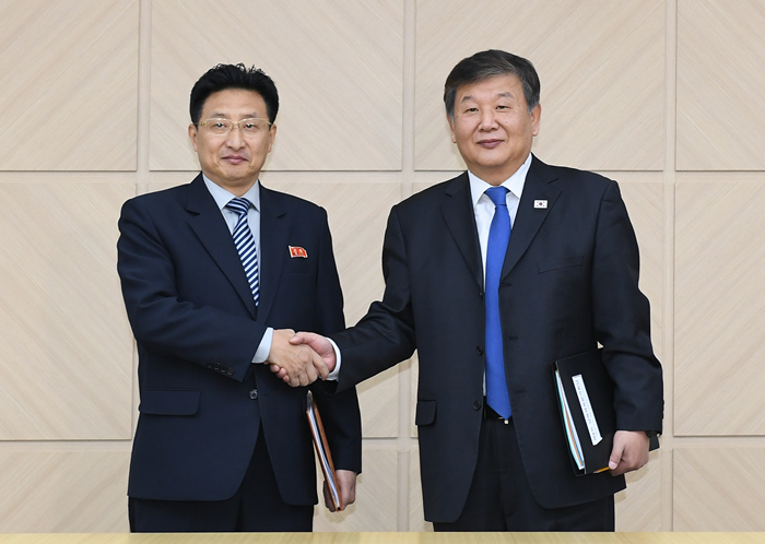 South Korean Deputy Culture, Sports and Tourism Minister Roh Tae-kang (right) and North Korean Vice Physical Culture and Sports Minister Won Kil-u on Dec. 14 shake hands at the inter-Korean joint liaison office in Gaeseong. (Ministry of Unification)