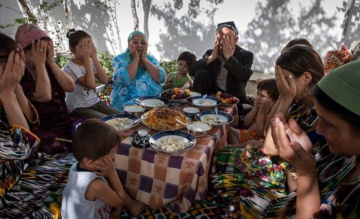 A family in Uzbekistan prays after eating a meal. (Sung Nam-hun).