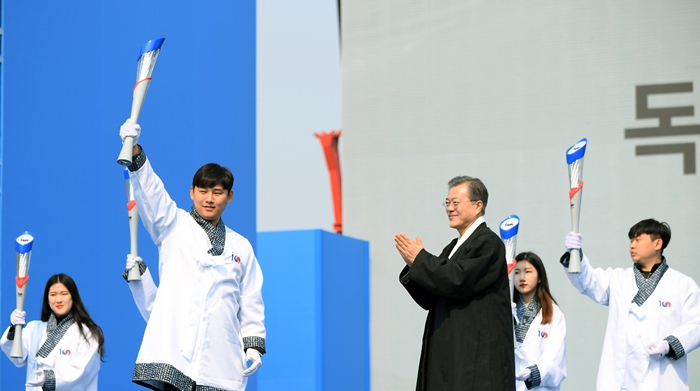President Moon Jae-in on March 1 hands over a torch to a young runner in a ceremony marking the centennial anniversary of the March First Independence Movement at Seoul's Gwanghwamun Square. (Hyoja-dong Studio)