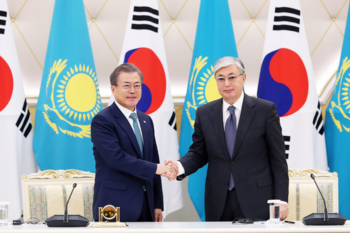 President Moon Jae-in (left) on April 22 shakes hands with Kazakh President Kassym Jomart Tokayev at a signing ceremony after their summit.