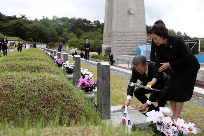 President Moon Jae-in and first lady Kim Jung-sook on May 18 lay flowers at the May 18 National Cemetery in Gwangju. (Cheong Wa Dae)