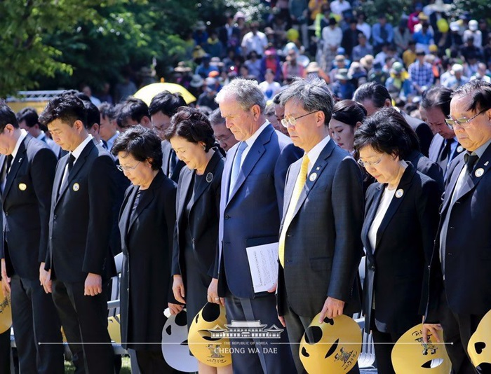 Attendants on May 23 pay a silent tribute at the memorial service for the tenth death anniversary of former President Roh Moo-hyun in Bongha Village of Gimhae, Gyeongsangnam-do Province. From left are the late president's son Roh Geon-ho, Roh's widow Kwon Yang-sook, first lady Kim Jung-sook and former U.S. President George W. Bush.